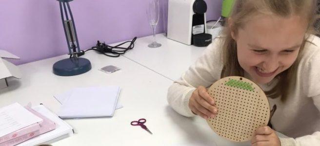 Child stitching the Mini Little Stitchers cross stitch subscription kit (Source: thegeekystitchingco.com)